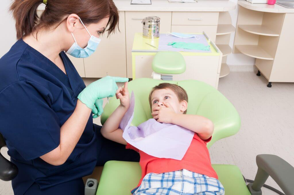 Woman dentist calming kid patient with games in dental office